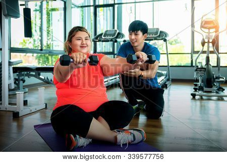 Asian Fat Girl Work Out And Weight Lifting With Her Trainer, This Image Can Use For Fat, Diet, Fitne