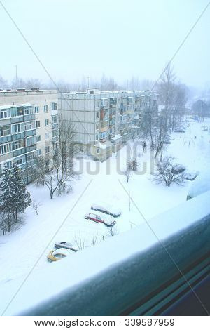 Bad Weather In Town. Thick Layer Of Snow On Window-sill Beyond Window. Urban Scene. Weather Concept.