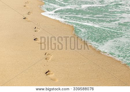 Beach, Wave And Footprints On Sand. Vacation Concept. Time, Life Passing Concept.