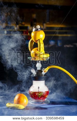 Hookah With A Round Transparent Flask In Which There Is A Red Liquid. Hookah Bowl Of Oranges And Ban