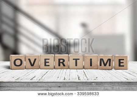 Overtime Word Spelled With Wooden Blocks In An Office Environment