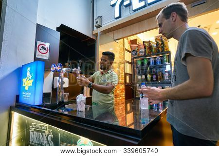 SINGAPORE - CIRCA APRIL, 2019: worker at 7-Eleven convenience store in Singapore. A convenience store is a small store that stocks a range of everyday items.