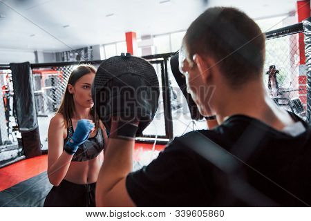 Behind The Fence. Athletic Young People Have Sparring On The Boxing Ring.