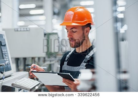 Making Notes. Industrial Worker Indoors In Factory. Young Technician With Orange Hard Hat.