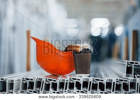 Bread Is On The Cup With Drink. Orange Hard Hat On Objects In The Factory. No People. Conception Of