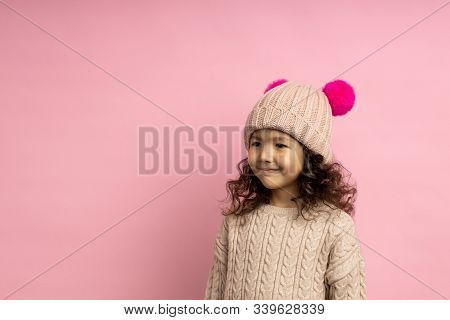 Studio Shot Of Friendly Little Child With Curly Hair, Wearing Beige Sweater And Knitted Hat With Pom