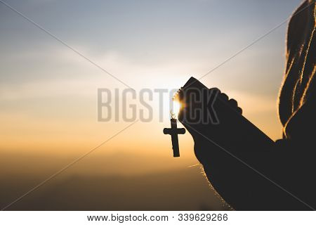Silhouette Of Young Woman Hands Holding Holy Bible And Lift Of Christian Cross, Religion Symbol In L
