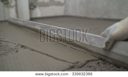 Leveling The Floor Of A Large Construction Spatula. The Worker Pours The Floors With Mortar. The Bui