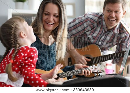Portrait Of Happy Smiling Parents And Daughter Spending Time Together. Mom, Father Looking At Kid Wi