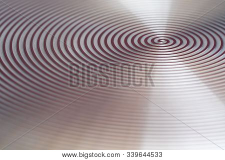 Red Spiral. Blurred Background. View Of The Aluminum Plate From The Side.