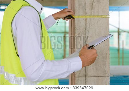 Young Foreman Builder, Engineer Or Inspector Checking And Inspecting With Clipboard And Measuring Ta