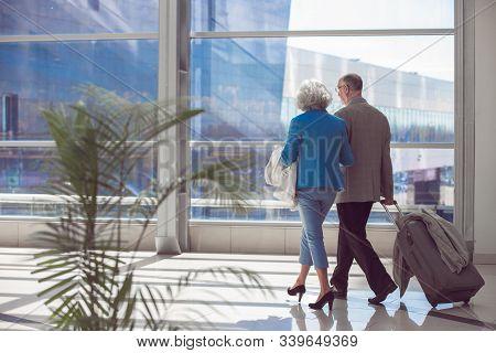 Happy Elderly Senior Couple Of Travelers With Suitcase In Airport