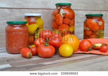 Preserved And Fermented Food In Glass Jars. Autumn Canning. Tomatoes Pickling And Canning Into Glass
