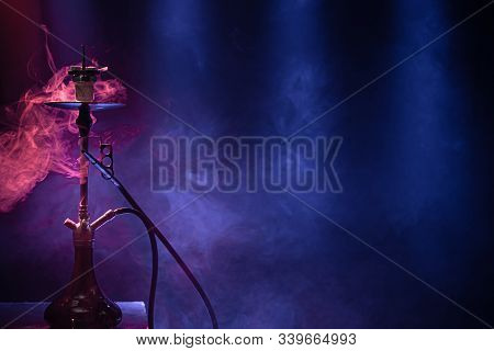 The Classic Hookah. Beautiful Background, With Colored Rays Of Light And Smoke. The Concept Of Hooka