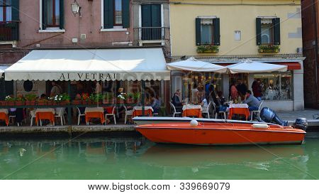 Murano, Venice, Italy - September 23, 2017: Canal Side  Restaurants And Poer Boat Murano Venice