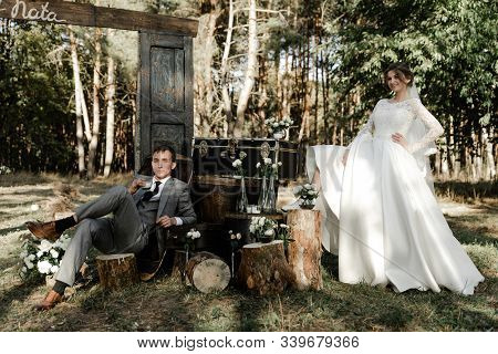 Attractive Couple Celebrating Their Wedding In Forest. Portrait Of Young Happy Groom And Bride In We