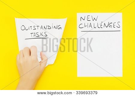 Hand Wrinkles A Piece Of Paper With Phrase: Outstanding Tasks, And Nearby Blank Sheet Of Paper With