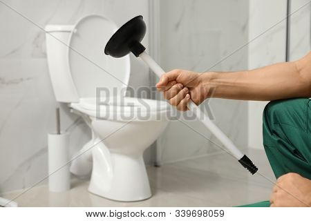 Professional Plumber Holding Plunger Near Toilet Bowl In Bathroom, Closeup