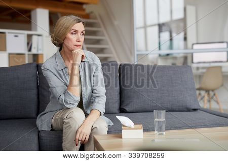 Portrait Of Elegant Mature Woman Sitting On Couch At Home And Looking Away Pensively, Sad Or Depress