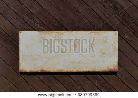 Old Tin Sign For Text Template On An Old Wooden Wall.