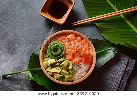 Hawaiian Salmon Poke Bowl With Avocado, Cucumber , Rice And Sesame Seeds Served In Bowl On Tropical