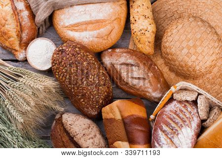 Assorted Whole Grain Bread Background. Wheat Ears And Various Types Of Artisan Bread. Bakery Concept