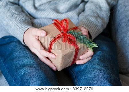 Female Hands Holding Gift Box With Red Ribbon And Fir Branch . Christmas, Hew Year, Birthday Concept