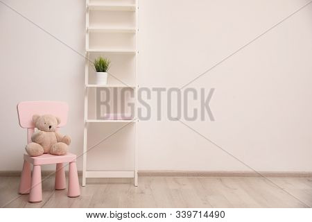 Teddy Bear On Chair And Shelving Unit Near Wall In Child Room. Space For Text