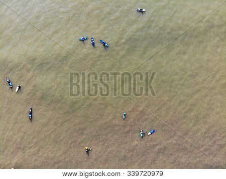 Aerial View Of Surfers Waiting The Waves In The Dark, Brown Water In Bali, Indonesia. Surfer On The