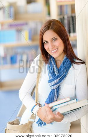 Smiling student girl hold education books high school library