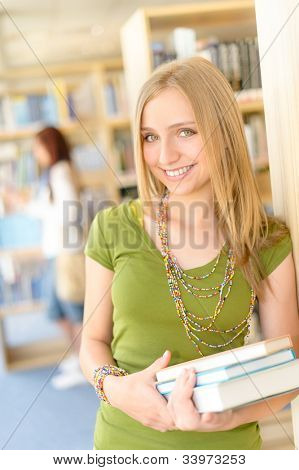 Happy female blonde student at library with books high school