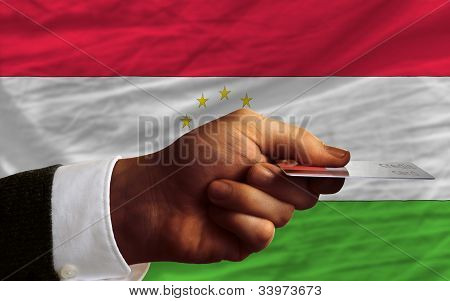 man stretching out credit card to buy goods in front of complete wavy national flag of tajikistan poster