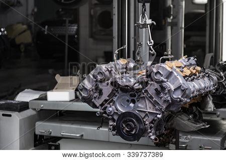 Used V8 Engine With Eight Cylinders Suspended Mounted On A Crane For Overhaul Repair And Installatio