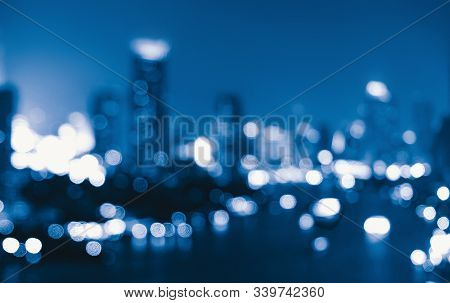 Bokeh Background Of Skyscraper Buildings In Downtown. Urban City With Lights, Blurry Photo At Night