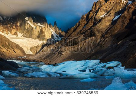 Cerro Torre coming out from the dramatic morning clouds at Laguna Torre lake full of icebergs. Los Glaciares National Park, Argentina