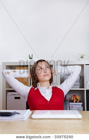 Relaxed woman sitting at her desk and looking up pensively