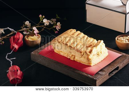 Tet Holiday Concept. Custard Cake On A Black Stone Plate With Red Paper