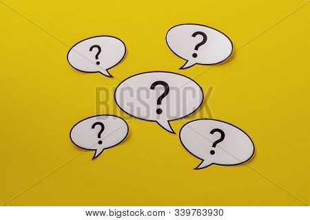 Five Speech Bubbles With Question Marks Over A Bright Yellow Background