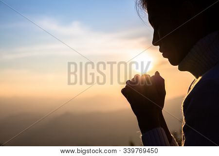 Woman Praying In The Morning On The Sunrise Background. Christianity Concept. Pray Background. Faith