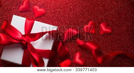 Valentine's Day Romantic Background with gift box and satin hearts. Date. Table setting with gift box over holiday red glittering background with hearts. Wedding celebrating