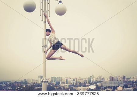 Girl Athlete Dancing On A Pole. Paul Dance On The Background Of The City. Striptease On The Lantern