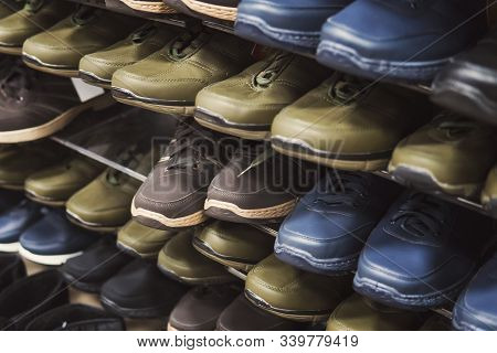 Close Up Of Shopping Stand With Budget-freindly Unisex Shoes For Autumn And Spring. Shelves With Men