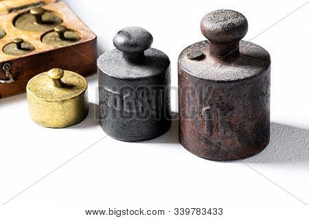 Old Rustic Metal Weights On White Background.