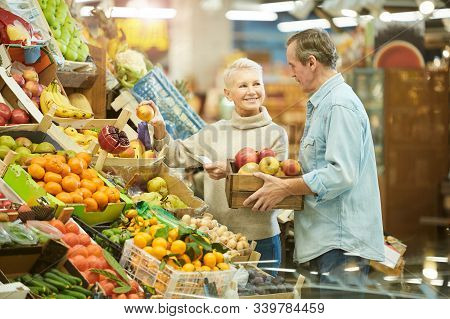 Waist Up Portrait Of Smiling Senior Couple Buying Fresh Fruits While Enjoying Grocery Shopping In Fa