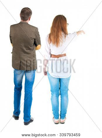 Back view of a stylish couple pointing. beautiful friendly girl and guy together. Rear view people collection. backside view of person. Isolated over white background.