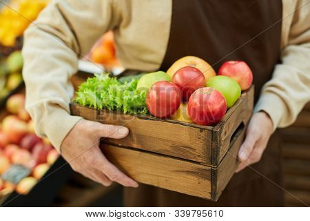 Close Up Of Unrecognizable Senior Man Holding Box Of Apples While Selling Fruits And Vegetables At F