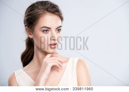 Portrait of a beautiful young woman with a brown hair. Pretty young female model with healthy skin of face - isolated on white background. Young attractive sexy girl looking to the camera
