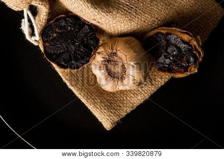 Black Garlic On Black Plate On Dark Background From Above. Culinary Food Ingredient.