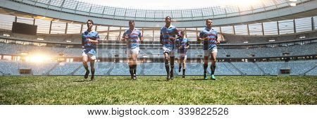 Rugby players against rugby stadium at dawn