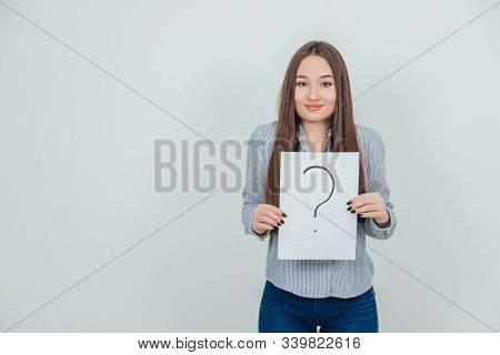 Inquisitive Asian Student Girl Holding A Sheet Of Paper With Question Mark Written On It.